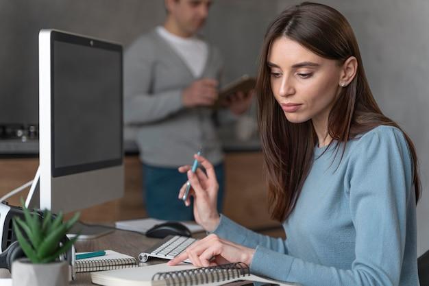 Seitenansicht der frau, die im medienfeld mit personal computer arbeitet