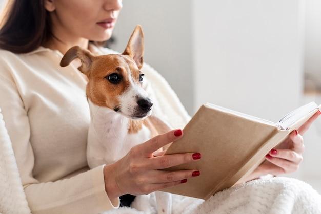 Seitenansicht der frau, die liest, während sie ihren hund hält