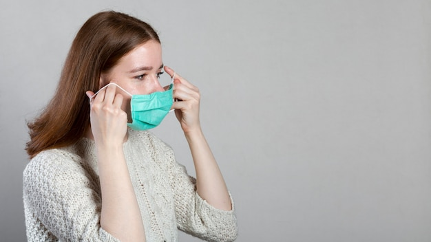 Seitenansicht der frau, die medizinische maske mit kopienraum aufsetzt