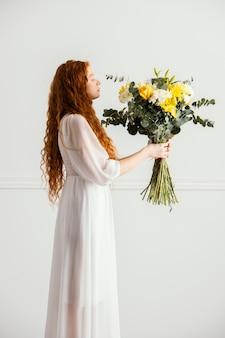 Seitenansicht der frau, die mit blumenstrauß der frühlingsblumen aufwirft