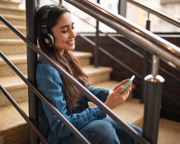 Seitenansicht der frau, die musik auf kopfhörer hört, während auf treppen sitzend