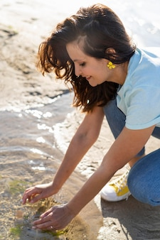 Seitenansicht der frau, die sauberes wasser in der natur genießt