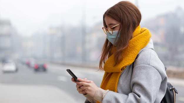 Seitenansicht der frau, die smartphone in der stadt beim tragen der medizinischen maske verwendet