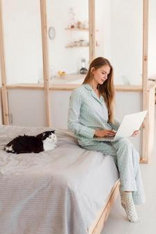Seitenansicht der frau, die von zu hause im schlafanzug mit katze arbeitet