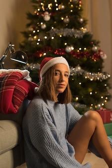 Seitenansicht der frau, die vor chrismas baum mit weihnachtsmütze aufwirft