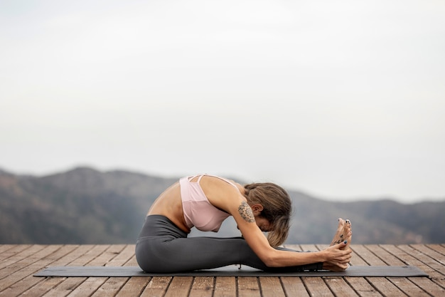 Seitenansicht der frau, die yoga draußen auf matte tut