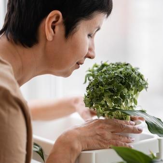 Seitenansicht der frau, die zimmerpflanze riecht