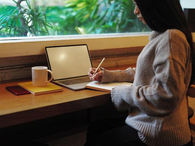 Seitenansicht der frau, die zur kenntnis nimmt, während sie mit modell-laptop auf hölzerner gegenstange im café arbeitet