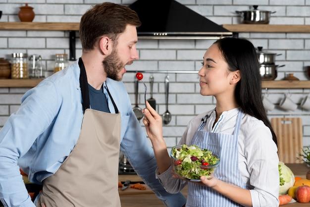 Seitenansicht der frau füttert kirschtomate ihren ehemann in der küche