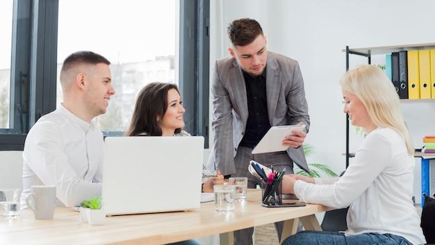 Seitenansicht der frau im rollstuhl, die an einem treffen bei der arbeit teilnimmt