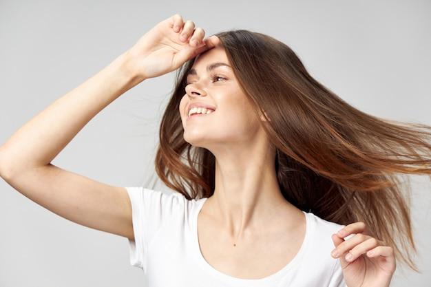 Seitenansicht der frau mit den langen haaren, die lächeln und hand nahe gesicht halten