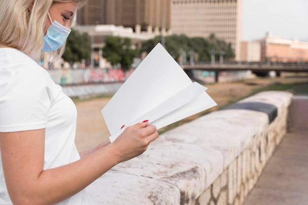 Seitenansicht der frau mit der medizinischen maske, die buch draußen mit kopienraum liest
