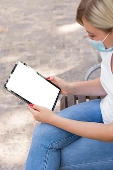 Seitenansicht der frau mit der medizinischen maske, die tablette hält