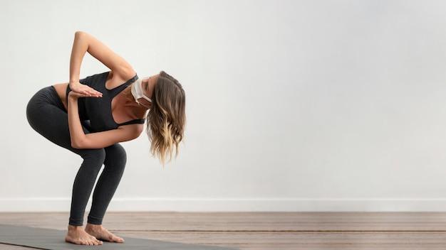 Seitenansicht der frau mit der medizinischen maske, die yoga mit kopienraum tut
