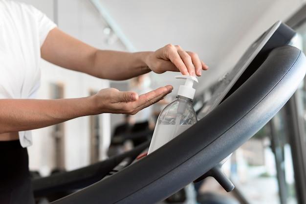 Seitenansicht der frau mit händedesinfektionsmittel im fitnessstudio