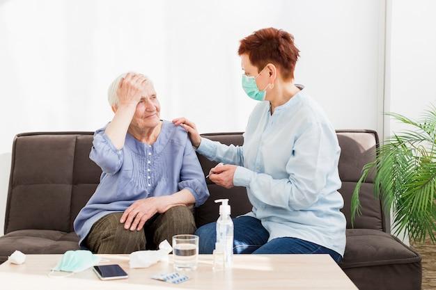 Seitenansicht der frau mit medizinischer maske, die sich um ältere frau kümmert