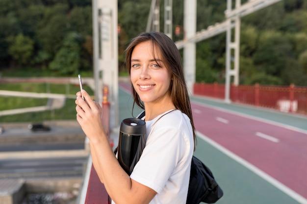 Seitenansicht der frau mit smartphone auf brücke während des reisens