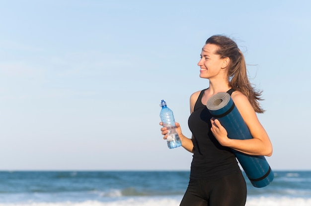 Seitenansicht der frau mit wasserflasche und yogamatte am strand