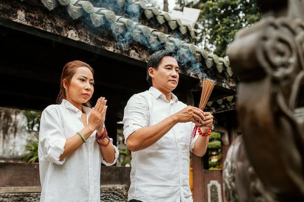 Seitenansicht der frau und des mannes, die am tempel mit brennendem weihrauch beten