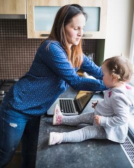 Seitenansicht der frau und ihrer tochter mit laptop auf küche worktop