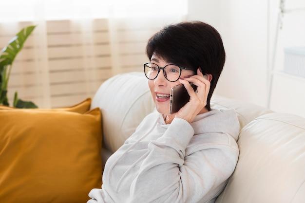 Seitenansicht der frau zu hause, die auf smartphone spricht