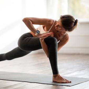 Seitenansicht der frau zu hause, die yoga-positionen ausübt