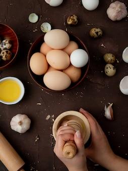 Seitenansicht der frauenhände, die knoblauch im knoblauchbrecher mit eiern und butter herum auf kastanienbraunem hintergrund drücken