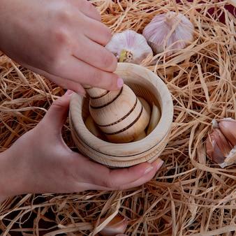 Seitenansicht der frauenhände, die knoblauch im knoblauchbrecher mit knoblauchknollen herum auf strohhintergrund drücken