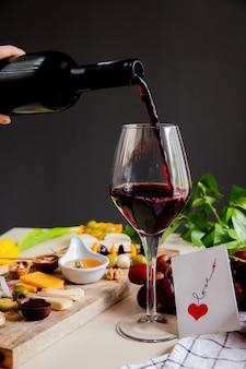 Seitenansicht der frauenhand, die rotwein in glas- und käseoliven-walnuss-traube und liebeskarte auf weißer oberfläche und schwarzer wand gießt