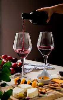 Seitenansicht der frauenhand, die rotwein in glas und verschiedene arten von käseoliven-walnuss-traube auf weißer oberfläche und schwarzem hintergrund gießt