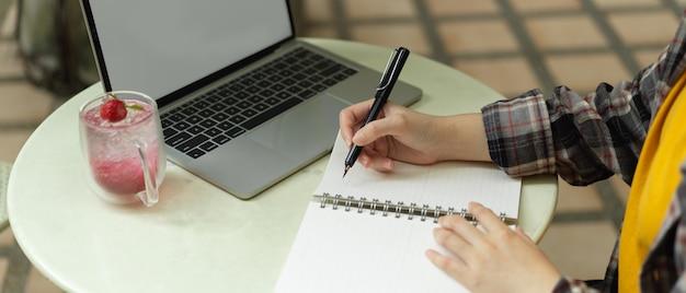 Seitenansicht der freiberuflerin, die auf zeitplanbuch notiert, während sie mit modell-laptop arbeitet