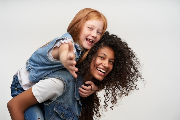 Seitenansicht der freudigen hübschen jungen dunkelhäutigen brünetten frau, die auf ihrem rücken fröhliches niedliches rothaariges weibliches kind reitet, glücklich schaut und breit lächelt, lokalisiert auf weiß