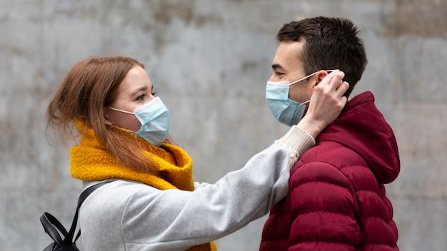 Seitenansicht der freundin, die die medizinische maske des freundes repariert Kostenlose Fotos