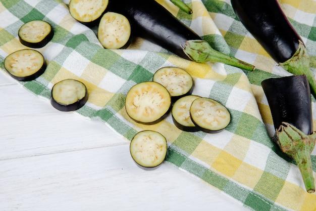 Seitenansicht der frischen aubergine mit gehackten scheiben auf kariertem stoff auf weißem rustikalem