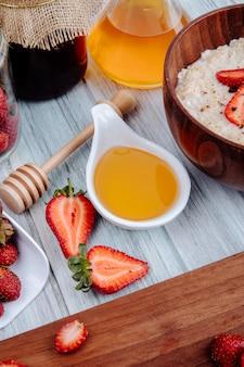 Seitenansicht der frischen reifen erdbeeren auf einem holzbrett mit honig und haferbrei in der holzschale auf rustikalem