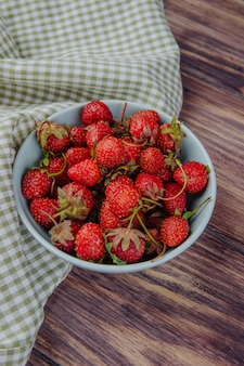 Seitenansicht der frischen reifen erdbeeren in einer schüssel auf holz rustikal