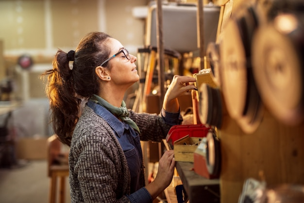 Seitenansicht der fröhlichen fleißigen industrieingenieurin mittleren alters mit brille, die werkzeuge aus den regalen in der werkstatt auswählt.