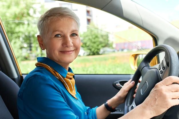 Seitenansicht der fröhlichen frau mittleren alters innerhalb des autos auf fahrersitz mit händen am lenkrad