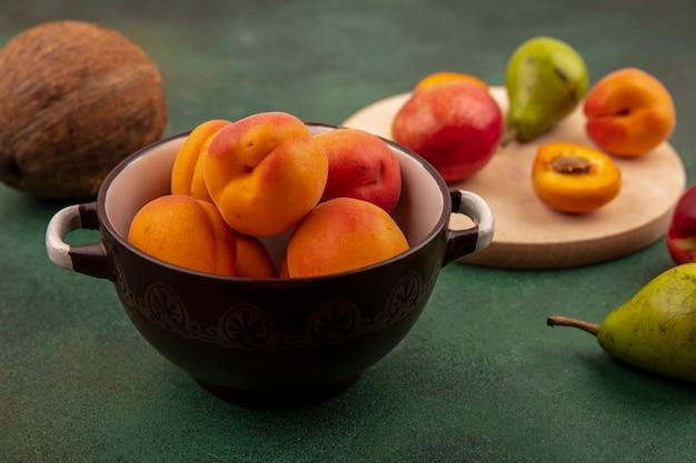 Seitenansicht der ganzen aprikosen in der schüssel und halb schneiden sie eine mit pfirsichbirne auf schneidebrett und kokosnuss auf grünem hintergrund