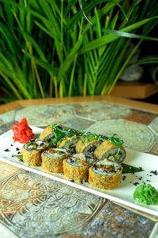 Seitenansicht der gebratenen sushi-rollen der traditionellen japanischen küche tempura mit aal serviert mit teriyaki auf grün