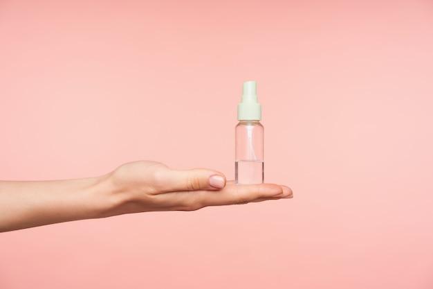 Seitenansicht der gepflegten weiblichen hand, die handfläche hält, während transparente sprühflasche mit flüssigkeit darauf hält, lokalisiert gegen rosa hintergrund