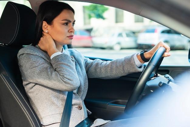 Seitenansicht der geschäftsfrau, die nackenschmerzen im auto hat