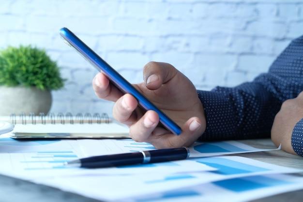 Seitenansicht der geschäftsmannhand unter verwendung des smartphones am schreibtisch