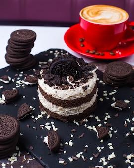 Seitenansicht der geschichteten kleinigkeit mit schokoladen-biskuit-schlagsahne, verziert mit kekskrümeln auf dem tisch