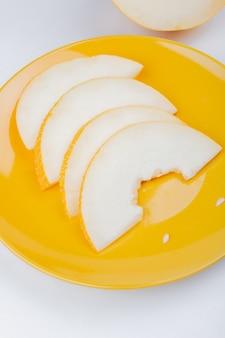 Seitenansicht der geschnittenen melone in auf weißem hintergrund