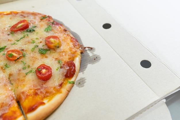 Seitenansicht der geschnittenen vegetarischen pizza - traditioneller schnellimbiß im peper kasten geöffnet.