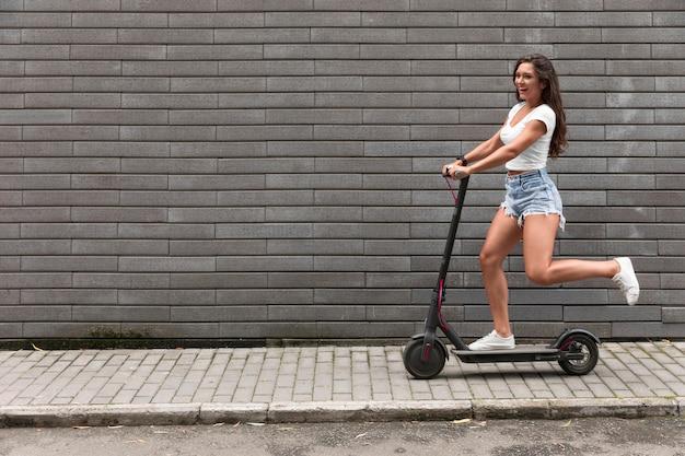 Seitenansicht der glücklichen frau, die einen elektroroller reitet