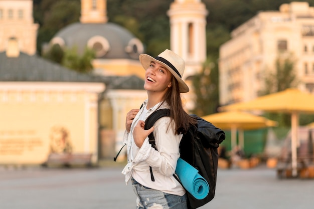 Seitenansicht der glücklichen frau mit hut, der rucksack während des reisens trägt