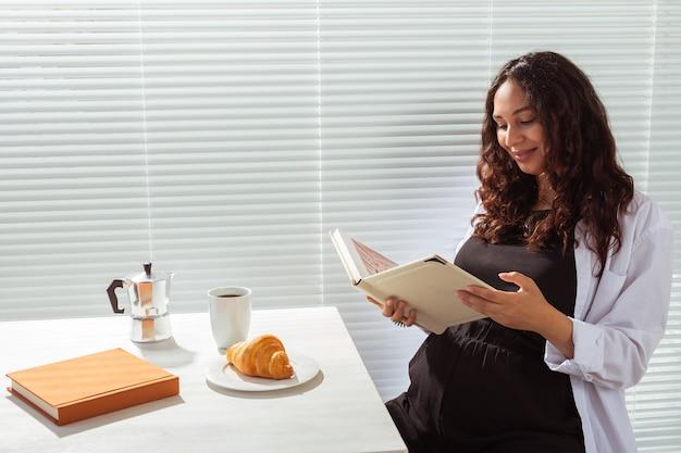 Seitenansicht der glücklichen jungen schönen frau, die buch liest, während sie morgenfrühstück mit kaffee hat