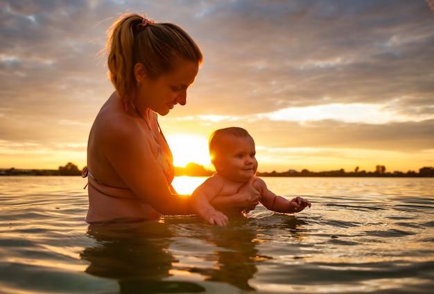 Seitenansicht der glücklichen mutter, die schwimmendes kleines schönes lächelndes baby im meerwasser lehrt